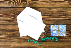 Envelope with message card and gift box on wooden table,. Envelope with message card and gift box with golden bow on wooden table, top view Royalty Free Stock Photos