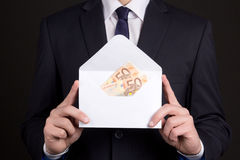 Envelope with money in business man hands. White envelope with money in business man hands Stock Images