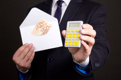 Envelope with money and calculator in business man hands Stock Images
