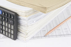 Envelope and overload of old paperwork with vertical calculator Royalty Free Stock Photos