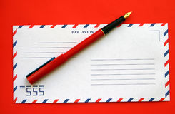 Envelope and pen. On a red background Stock Photography