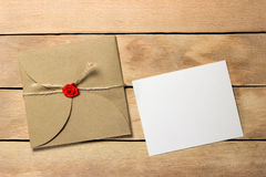 The envelope and a piece of text. On a wood background Stock Photos