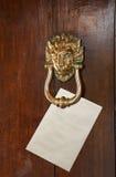 Envelope placed under door knocker Stock Photo