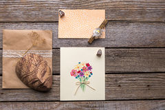 Envelope, postcard and mask on a wooden background. Royalty Free Stock Image