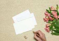 Envelope and postcard with flowers on stone background stock photo