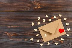 Envelope and red hearts from brown Kraft paper on wooden aged vintage background. Valentine`s day Greeting stock images