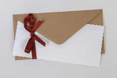 Envelope with red ribbon Stock Image