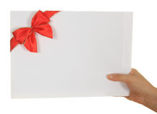 Envelope with red ribbon in hand Stock Image