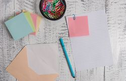 Front view open colored rectangular envelope blank sheet paper stacked sticky note pads ballpoint clips holder lying. Envelope sheet paper sticky note pads pen stock photos