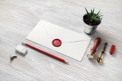 Envelope and stationery. Blank paper envelope with red wax seal and stationery on light wooden background. Mockup for your design stock photo