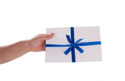 An envelope with a thin blue ribbon in the hands. Isolated on white Royalty Free Stock Images