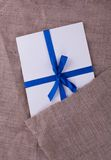 The envelope tied with a blue ribbon on sacking. The envelope tied with a blue ribbon Stock Photography