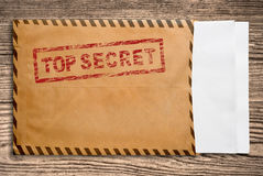 Envelope with top secret stamp and blank papers. Open yellow envelope with top secret stamp and blank papers, on wooden table, clipping path Stock Photography