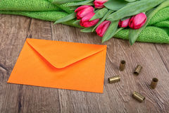 Envelope, tulips and bullets on a wooden background Stock Photo