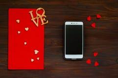 Envelope vermelho com corações e um smartphone em um fundo de madeira, o conceito do dia do ` s do Valentim, vista superior Fotografia de Stock Royalty Free
