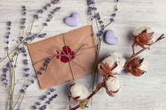 Envelope with wax seal and lavender on wooden background. Royalty Free Stock Image