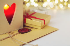 Envelope with wax seal surrounded by gift and a candle in the wooden box with heart shaped hole Royalty Free Stock Photo
