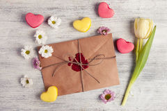 Envelope with wax seal and tulip on wooden background. Stock Photo