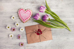 Envelope with wax seal and tulips on wooden background. Royalty Free Stock Images