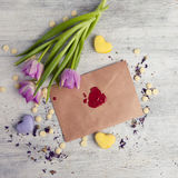 Envelope with wax seal and tulips on wooden background. Stock Photography