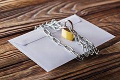 Envelopes com letras e cadeado, corrente no fundo de madeira velho Proteção de seu cargo, enviamento do PC Placas para o desenhis imagem de stock