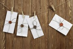 Envelopes pinned to rope. Envelopes hanging on rope on wooden background Stock Images
