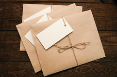 Envelopes from kraft pape. Note from a paper on a cord of an envelope from kraft paper on a wooden table Royalty Free Stock Photo