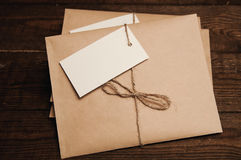 Envelopes from kraft pape. Note from a paper on a cord of an envelope from kraft paper on a wooden table Stock Image