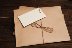 Envelopes from kraft pape. Note from a paper on a cord of an envelope from kraft paper on a wooden table Stock Photo