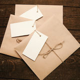 Envelopes from kraft paper. Note from a paper on a cord of an envelope from kraft paper on a wooden table Royalty Free Stock Photo