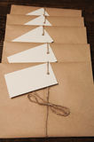 Envelopes from kraft paper. Note from a paper on a cord of an envelope from kraft paper on a wooden table Stock Images