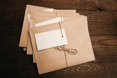 Envelopes from kraft paper. Note from a paper on a cord of an envelope from kraft paper on a wooden table Royalty Free Stock Photography