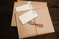 Envelopes from kraft paper. Note from a paper on a cord of an envelope from kraft paper on a wooden table Royalty Free Stock Images