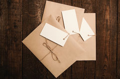 Envelopes from kraft paper. Note from a paper on a cord of an envelope from kraft paper on a wooden table Stock Photos