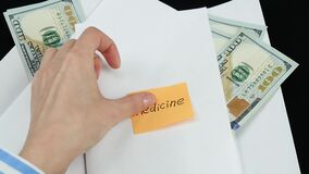 Envelopes with money on lie on the table. The hand of an unknown person sticks a sticker with the words `medicine` on an