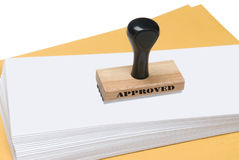 Envelopes and rubber stamp of approval. A rubber stamp of approval ready to be used to stamp envelopes Stock Images