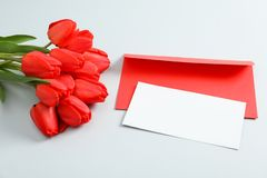 Envelopes with space for text and beautiful red tulips on light grey background. Closeup stock photos