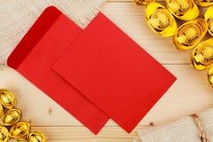 Envelopes vermelhos e lingote chinês do ouro no fundo de madeira Fotos de Stock Royalty Free