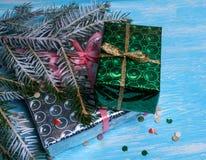 Enveloppé dans les cadeaux de papier de Noël et la branche verte de sapin sur un fond clair Images stock