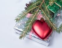 Enveloppé en cadeaux de papier brillants se trouvant sur leur coeur image libre de droits