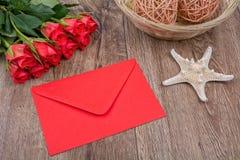 Enveloppe, étoiles de mer et roses sur un fond en bois Image libre de droits
