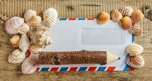 Enveloppe avec des coquillages sur une table en bois image libre de droits