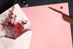 Enveloppe avec des fleurs sur un papier et un stylo de cannette Photographie stock libre de droits