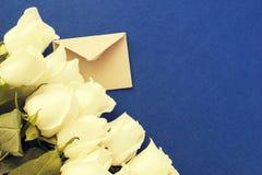 Enveloppe avec le bouquet de roses blanches au-dessus du fond bleu Lettre d'amour ou carte d'invitation Image stock