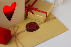 Enveloppe avec le joint de cire entouré par des cadeaux et une bougie Image stock