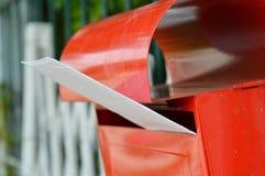 Enveloppe blanche dans la boîte aux lettres rouge sur la barrière à la maison photos stock