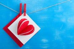 Enveloppe blanche de carte cadeaux et de rouge sur le fond en bois bleu Images stock
