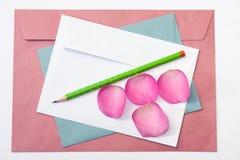 Enveloppe blanche et bleue rouge avec un peta en bois de rose de stylo et de rose Image stock