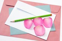 Enveloppe blanche et bleue rouge avec un peta en bois de rose de stylo et de rose Image libre de droits
