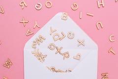Enveloppe blanche ouverte avec beaucoup de lettres d'ABC sur le fond rose image stock